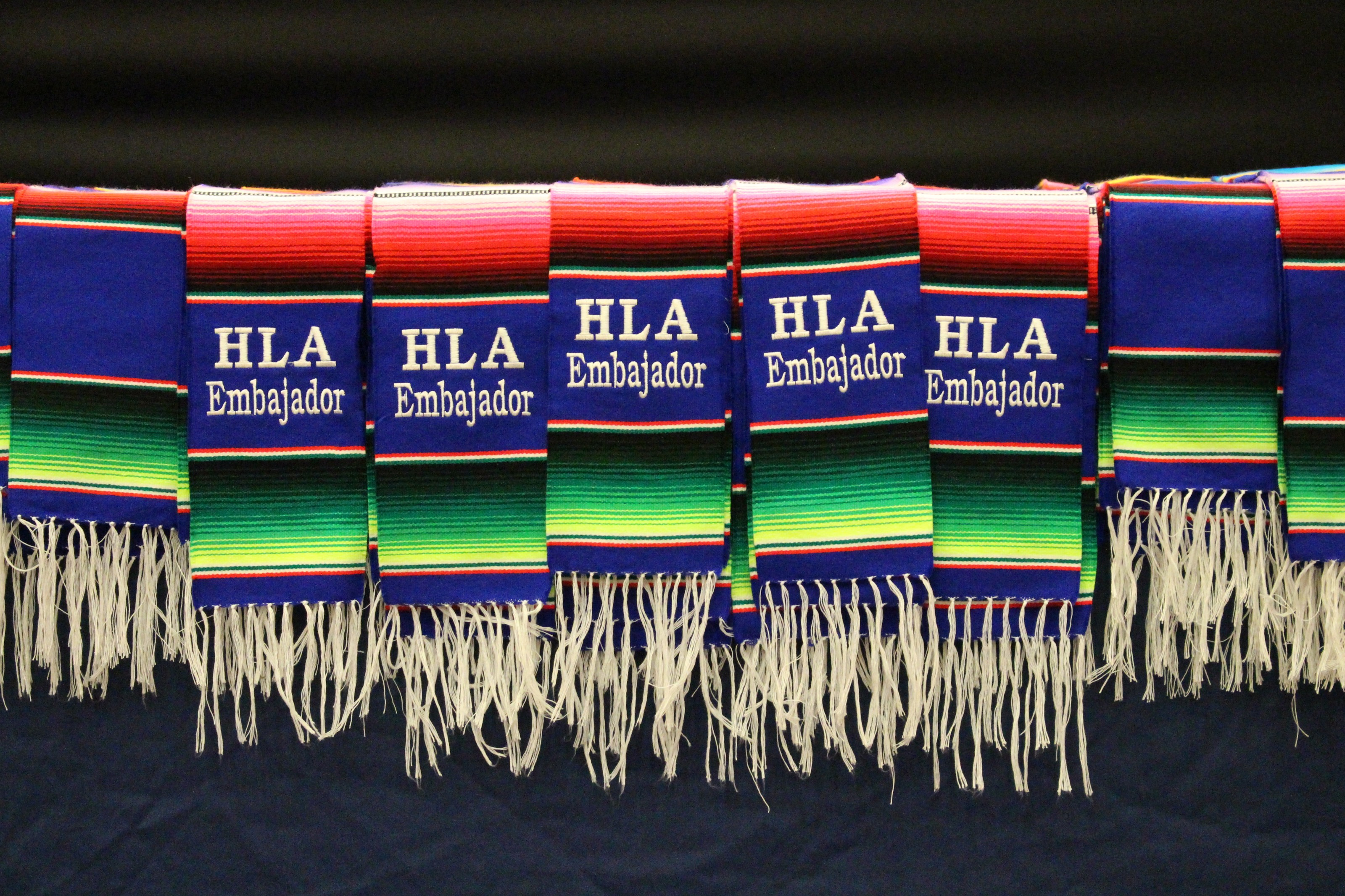 Serape style graduation stoles with embroidery reading HLA Embajador